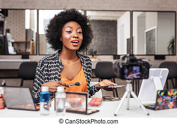 Cute dark-skinned woman with coral lipstick taking looking enthusiastic