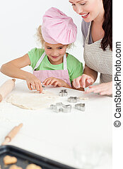 Cute daughter and her beautiful mother making cookies using baking tins in the kitchen