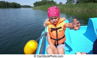 Cute daughter girl sitting in catamaran with life vest jacket wave hand. Gimbal motion shot.
