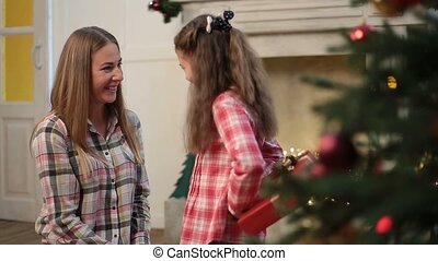 Cute daughter giving Christmas gift to mother
