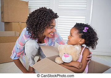 Cute daughter sitting in moving box holding teddy with ...
