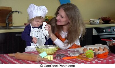 cute daughter with mother put flour on nose. Playful family girls in kitchen