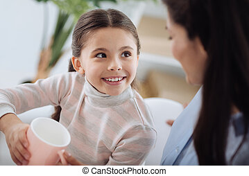 Cute delighted girl holding a cup of tea