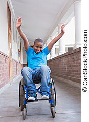 Cute disabled pupil smiling at camera in hall at the...
