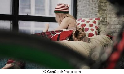 Cute dog in red jacket is peacefully sleeping near his mistress on the bed. The female is playing with her baby, looking over her sholder and smiling