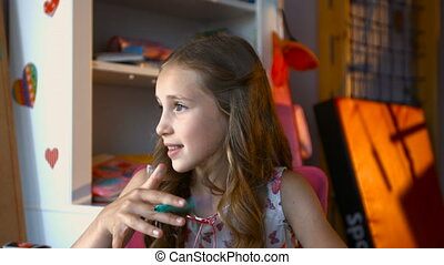 Cute dreamy little girl holding markers searching for ideas while sitting at table