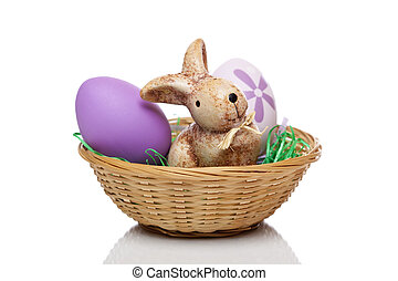 Cute Easter bunny sitting in basket with eggs