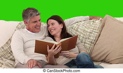 Cute elderly couple looking at an album