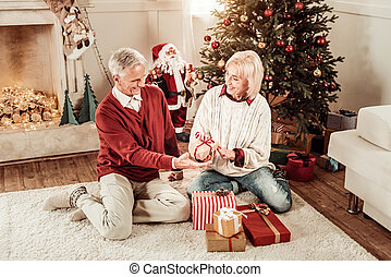 Cute elderly couple sitting and overlooking presents.