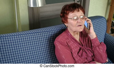 Cute elderly woman talking on the phone. grandmother.