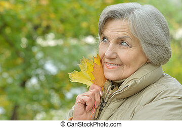 Cute elderly woman walking in the park