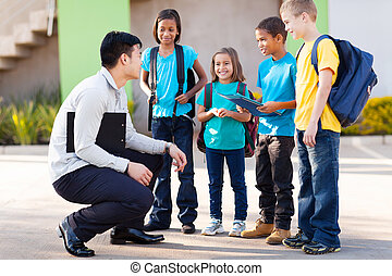 elementary pupils outside classroom talking to teacher -...
