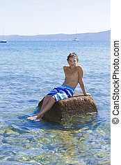 Cute eleven years old boy sitting on a rock in the sea