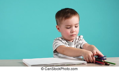 Cute European Boy Draws Sitting at Table With Colored Pencils in Album.