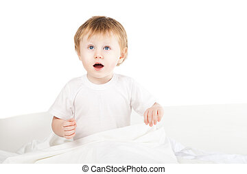 cute excited baby girl in bed at home over white
