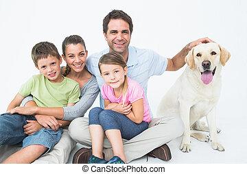 cute, família, com, animal estimação, labrador, posar, e, sorrindo, câmera, junto, branco, fundo