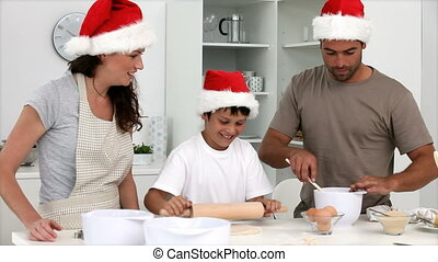 Cute family cooking christmas cakes in the kitchen at home