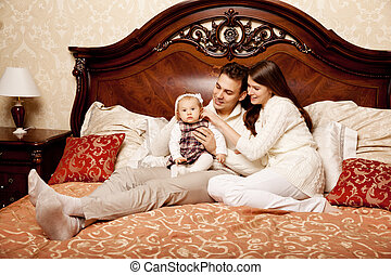 Cute Family In The Bedroom Mother Father And Daughter In The I