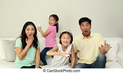 Cute family playing video games on