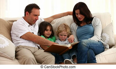 Cute family reading a book while sitting on the sofa at home
