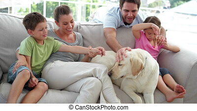 Cute family relaxing together on the couch with their dog in...