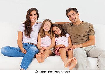 Cute family sitting on a sofa