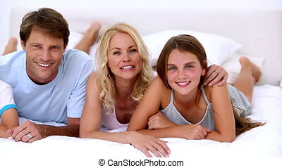 Cute family smiling at the camera together at home on bed