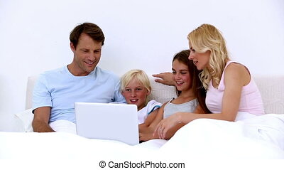 Cute family using laptop together at home in bed