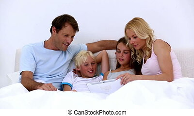 Cute family using tablet together at home in bed