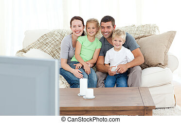 Cute family watching television on the sofa at home