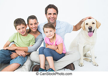 Cute family with pet labrador posing and smiling at camera together on white background