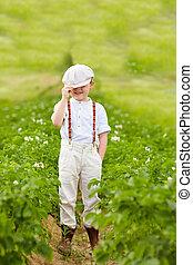cute farmer boy in potato rows