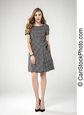 cute fashion blonde model posing in pleated gray dress. white background . standing. studio shot.