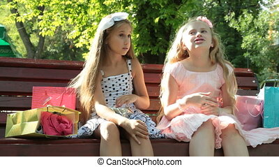 Cute fashion little girls conversation on a bench
