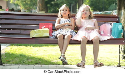 Cute fashion little girls in summer dresses conversation on a bench