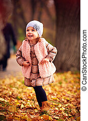 cute fashionable baby girl walking in autumn park among fallen leaves