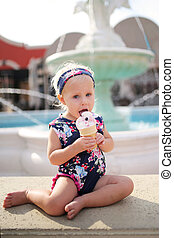 Cute, Fashionable One Year Old Baby Girl Eating Ice Cream Cone Outside Restaurant