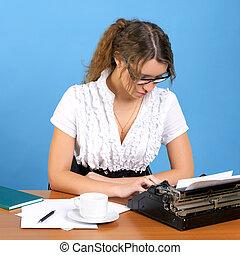 Cute female author with vintage typewriter writing something