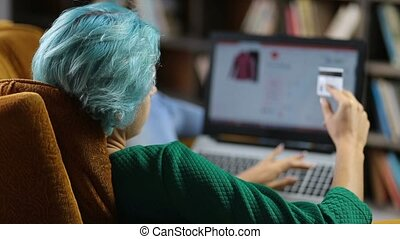 Cute female customer shopping online with laptop