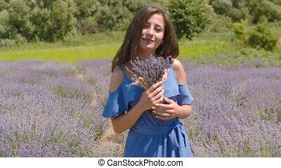 Cute female enjoying fragrant of lavender flowers - Carefree...