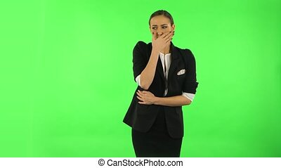 Cute female feels bad, her stomach hurts, feeling nausea. Girl with dark hair wearing a black business suit at green screen at studio.