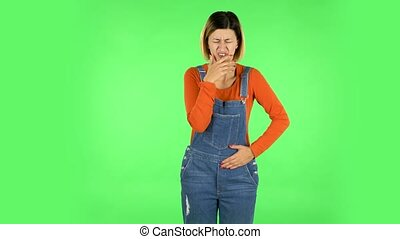Cute female feels bad, her stomach hurts, feeling nausea. Brown-eyed girl with an earring in her ear dressed an orange sweater and denim overalls on a green screen in the studio