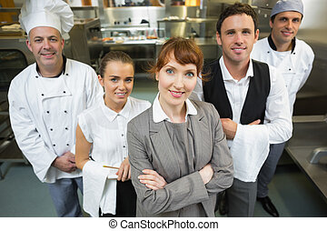 Cute female manager posing with the staff in a modern...