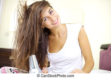 Cute female model with wet hair drying it in bed