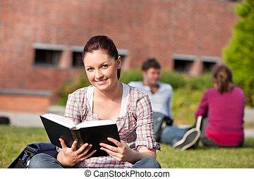 Cute female student reading a book