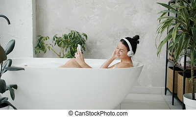 Cute female student is relaxing listening to pop music and using smartphone touching screen in bathtub in apartment. Youth culture and devices concept.