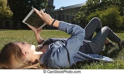 Cute female student studying with tablet in park -...