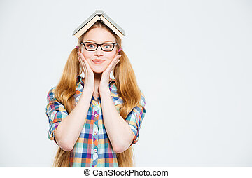 Cute female student with book on head