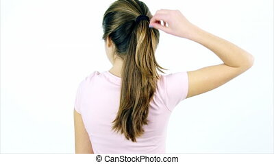 Cute female teenager undoing ponytail of long hair ok sign -...