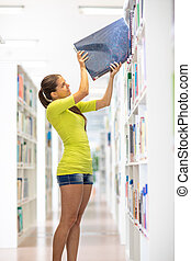 Cute female university student in library